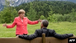 German Chancellor Angela Merkel (left) gestures while chatting with U.S. President Barack Obama sitting on a bench outside the Elmau Castle after a working session of a G7 summit near Garmisch-Partenkirchen on June 8.