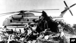 The remains of a burned-out U.S. helicopter lies in front of an abandoned chopper in the eastern desert region of Iran Saturday April 27, 1980, one day after the aborted American Commando raid to free the U.S. embassy hostages. (AP Photo)