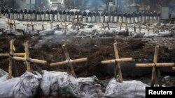 Арнайы жасақ шеру кезінде қаза тапқан және жоғалған адамдарға қойылған белгілердің ар жағында тұр. Киев, 11 ақпан 2014 жыл.