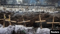 Near the barricades in Kyiv, riot police stand behind crosses installed by anti-government protesters in memory of the people who have died and went missing.