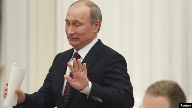 Russian President Vladimir Putin gestures as he arrives for a meeting with G20 summit participants in the Kremlin on February 15.