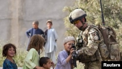 A British Army Major shows his rifle to Afghan children during a patrol near Lashkar Gah, the capital of Helmand Province.