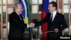 Brazilian Vice President Michel Temer (left) and Russian Prime Minister Dmitry Medvedev exchange documents during a signing ceremony in Brasilia on February 20.