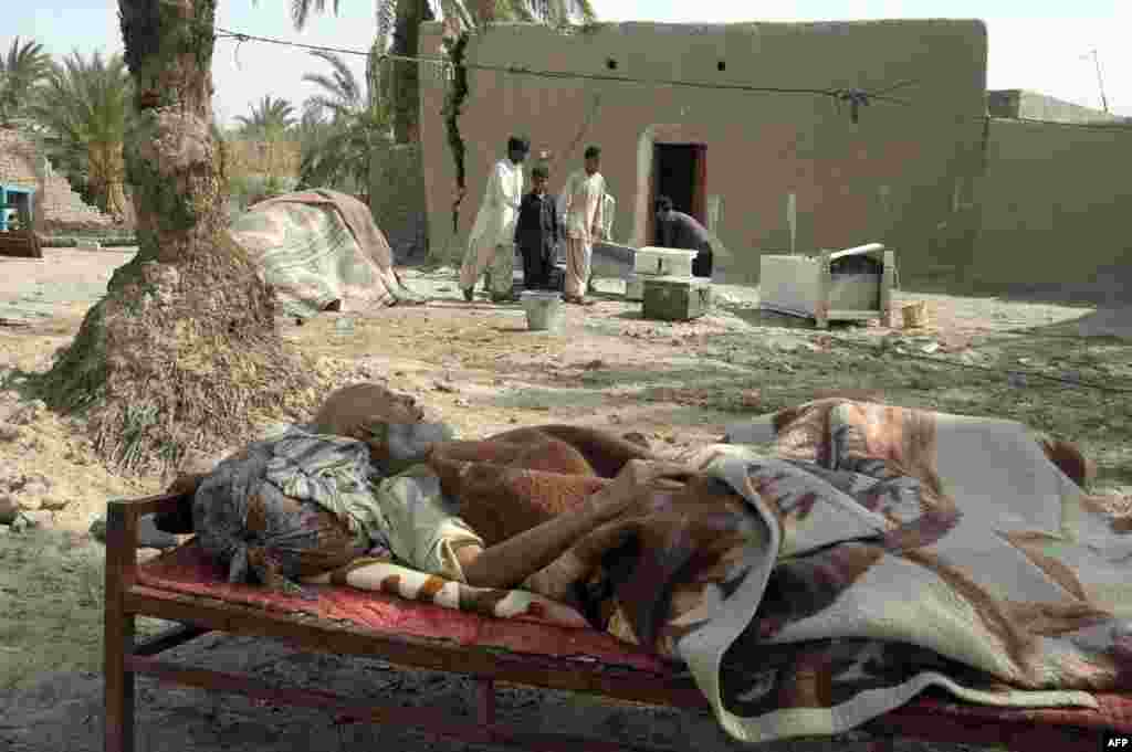 """An elderly earthquake survivor rests on a """"charpai"""" (wooden bed) outside his damaged mud house in the Mashkail area of southwest Balochistan Province. (AFP/Banaras Khan)"""