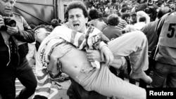Болельщик выносит раненого друга после обрушения стены на финальном матче Еврокубка в игре «Ювентуса» против «Ливерпуля». Брюссель, 29 мая 1985 года.