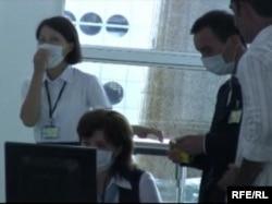 Сотрудники аэропорта в Казахстане в защитных масках во время распространения в мире эпидемии свиного гриппа. 30 июля 2009 года.