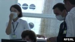 Сотрудники международного аэропорта в противовирусных масках. Алматы, 30 июля 2009 года.