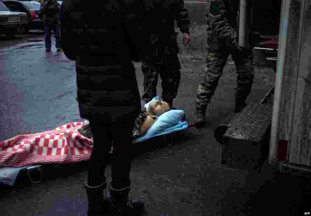 Ukrainian servicemen bring a wounded comrade to a hospital in the eastern Ukrainian city Artemivsk, in the Donetsk region.