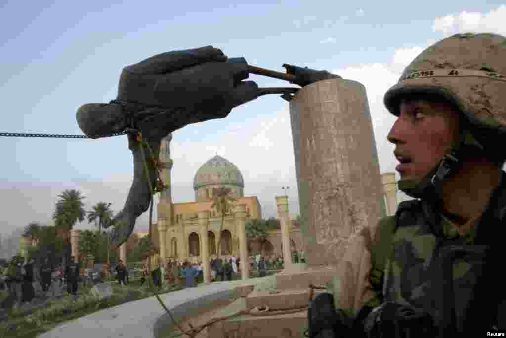 A U.S. Marine watches as a statue of Iraqi President Saddam Hussein falls in Firdos Square in Baghdad on April 9, 2003.