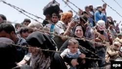 Беженцы на сирийской стороне пограничного перехода возле Акчакале (Турция) 10 июня 2015