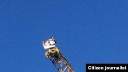 Молодой человек взобрался со своим плакатом на строительный кран в центре столицы