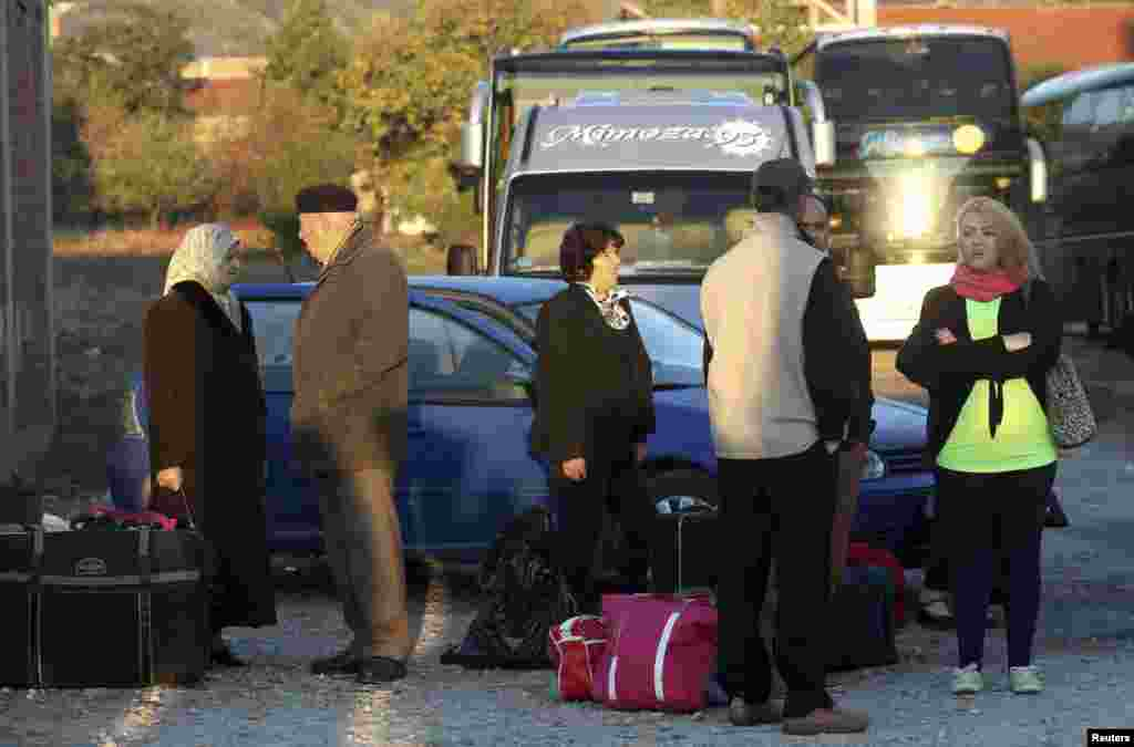 Ethnic Albanians wait for a bus to travel to the EU.