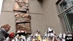 Një grua duke vendosur lule të krijuara nga letrat e gazetave në 8 vjetorin e përkujtimit të vrasjes së gazetares ruse Politkovskaya