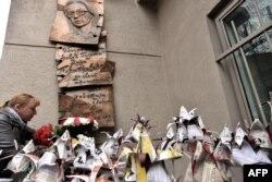 Жінка кладе квіти до меморіальної дошки в пам'ять вбитої російської журналістки Анни Політковської під час мітингу з нагоди восьмої річниці її смерті в Москві, 7 жовтня 2014 року