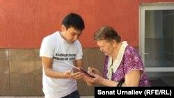 Гражданский активист Азамат Муханов беседует с местной жительницей в рамках опроса жителей города. Уральск, 25 сентября 2015 года.