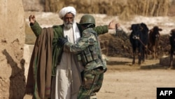 An Afghan soldier frisks a farmer during a patrol in Helmand Province.