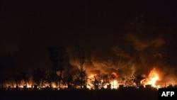 Полымя і дым па-над горадам Цяньцзінь пасьля сэрыі выбухаў у прамысловай зоне гораду. 13 жніўня 2015 году