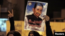A protester holds a poster of human rights activist Abdulhadi al-Khawaja during an antigovernment rally in Manama on April 8.