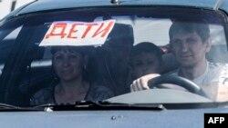 """Люди в автомобиле, на лобовом стекле которого - плакат с надписью: """"Дети"""". Иллюстративное фото."""