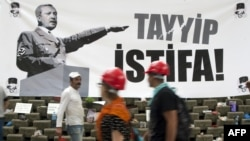 People on Istanbul's Taksim Square pass a banner calling on Prime Minister Recep Tayyip Erdogan to resign.