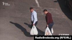 Двоє чоловіків несуть пакети з продуктами до управління СБУ