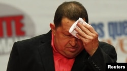 Venezuela -- Venezuela's President Hugo Chavez wipes his face after arriving at a rally with supporters prior to his trip to Cuba in Caracas, 23Feb2012