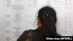 Девушка смотри на список вакансий, размещенный на стенде на ярмарке вакансий. Шымкент, 19 апреля 2018 года.