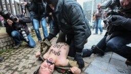"""Fondatoarea FEMEN Inna Shevchenko, arestată în fața Consiliului European din Bruxelles în timpul unui protest împotriva vizitei lui Vladimir Putin, ianuarie 2014. Corespundentul Europei Libere Dan Alexe se află în fundal. Pe pieptul Innei Shevchenko scrie: """"Good job, Putin !"""""""
