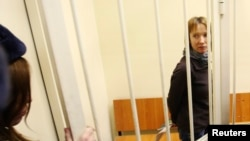 "Yekaterina Zaspa, who was a doctor aboard the ""Arctic Sunrise"" and is one of 30 people arrested over the Greenpeace protest at the ""Prirazlomnaya"" oil rig, in the dock in St. Petersburg at her November 18 hearing"