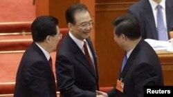 Кызмат мөөнөтү аяктап жаткан премьер -министр Вэн Цзябао болочок президент Си Цзинпин менен кол алышууда. 5-март, 2013-жыл.