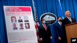 Издөөгө алынган орус хакерлеринин сүрөттөрү бар көрнөктүн жанында Федералдык иликтөө бюросунун (ФИБ) өкүлү Майкл Кристман (оңдо), Улуттук коопсуздук бөлүмүнүн өкүлү Жон Демерс (солдо) жана ФИБдин директорунун орун басары Дэвид Боудич турат. Вашингтон. 2020-жылдын 19-октябры.