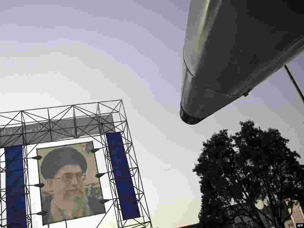 A display long-range surface-to-surface Shahab-3 missile is pictured in front of a portrait of Iran's supreme leader, Ayatollah Ali Khamenei, in a main square outside the parliament building in southern Tehran on September 23 as the Islamic republic marks Sacred Defense Week, which commemorates its bloody 1980-88 war with Iraq. Photo by Behrouz Mehri for AFP