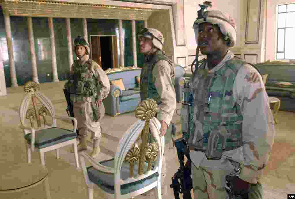 U.S. soldiers observe the reception room of a presidential palace near the international airport southwest of Baghdad.