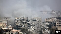 Smoke billows following Syrian government bombardment on the rebel-held besieged town of Harasta, in eastern Ghouta.