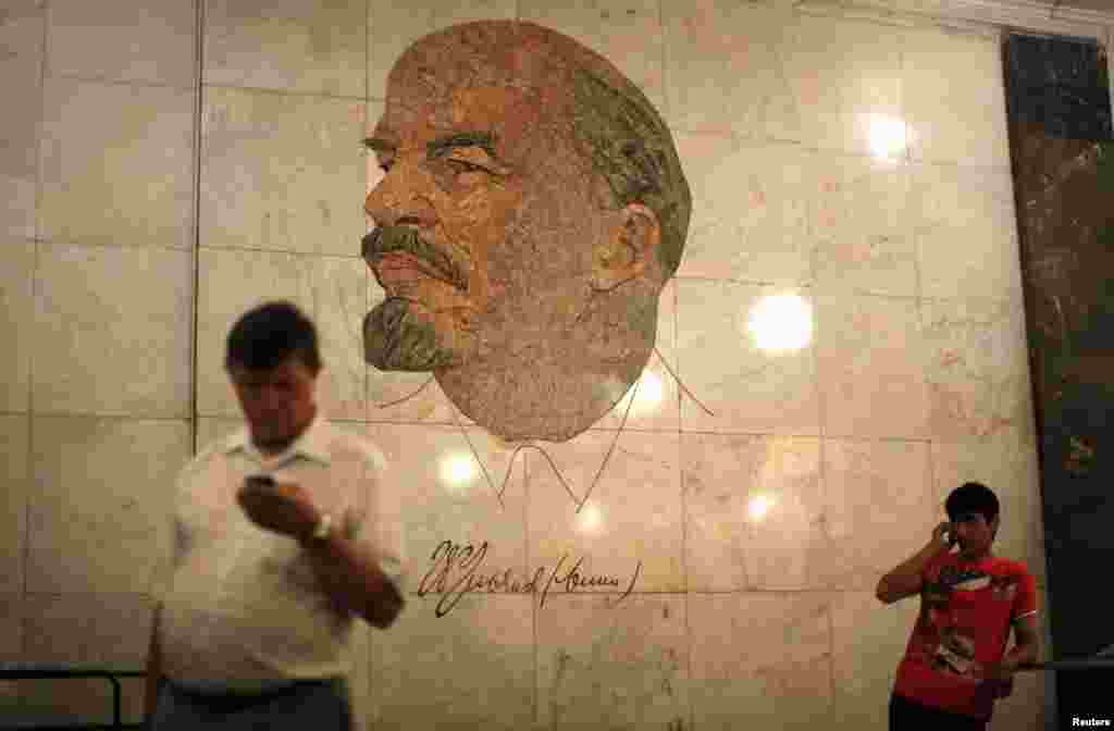 Men stand in front of a mosaic depicting former Soviet leader Vladimir Lenin at the Biblioteka Imeni Lenina metro station in Moscow.