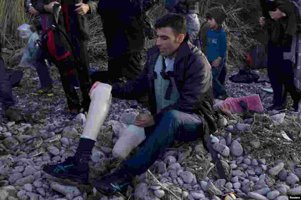 An Afghan refugee prepares to put on his prosthetic leg moments after arriving on an overcrowded dinghy on the Greek island of Lesbos, after crossing a part of the Aegean Sea from the Turkish coast. (Reuters/Dimitris Michalakis)