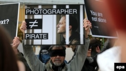 "A man holds up a placard in support of photojournalist Denis Sinyakov, who was among those detained on the Greenpeace ship ""Arctic Sunrise,"" in St. Petersburg on October 13."