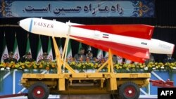 President Mahmud Ahmadinejad (center-left) watches as a Yasser missile is paraded during Army Day celebrations in Tehran.