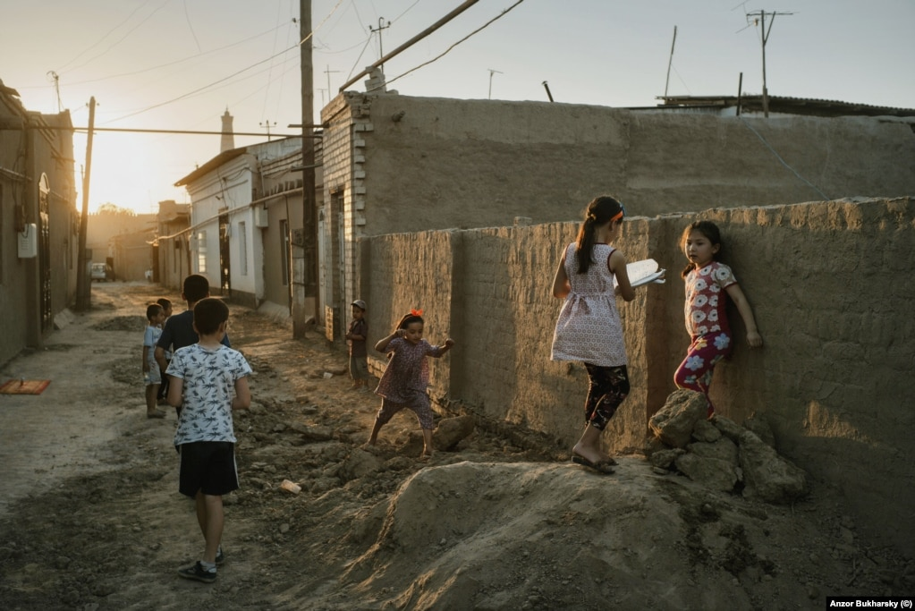 Local children play on one of the streets of old Khiva on a warm evening.