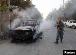 An Afghan policeman walks past a burning vehicle in the city of Kunduz on October 1