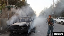 An Afghan policeman patrols next to a burning vehicle in Kunduz on October 1.