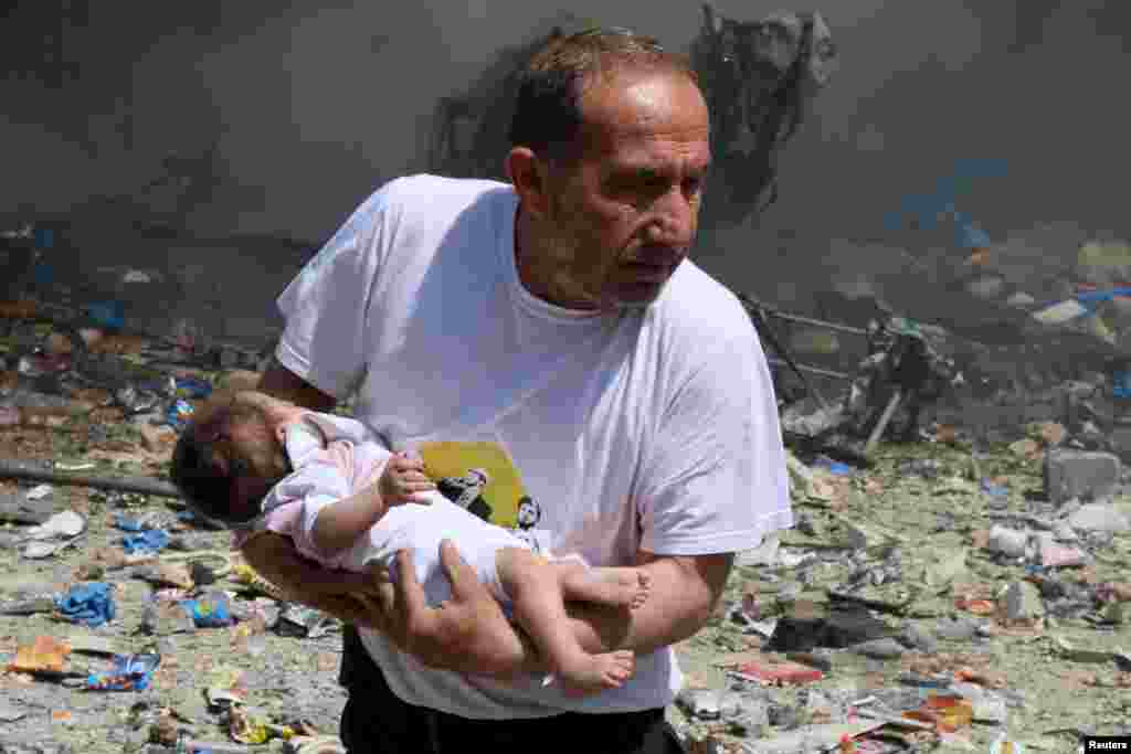 A man holds a baby that survived what activists said was a site hit by a barrel bomb dropped by Syrian government forces in the old city of Aleppo on June 3. (Reuters/Abdalrhman Ismail)