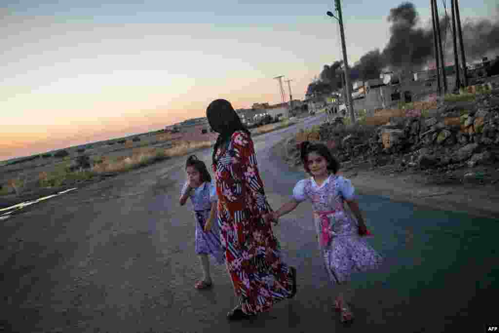 Girls walk with their mother as she turns to look at smoke billowing from three shells dropped on the town of Al-Bara in the northwestern Syrian province of Idlib. (AFP/Daniel Leal-Olivas)