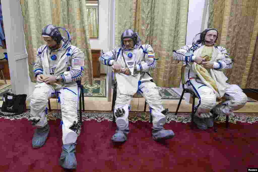 U.S. astronaut Christopher Cassidy (left) and Russian cosmonauts Alexander Misurkin (right) and Pavel Vinogradov put on space suits before taking part in a training exercise on a simulator at the cosmonaut training center at Star City outside Moscow. The three-man crew is due to blast off to the International Space Station on March 28. (Reuters/Sergei Remezov)