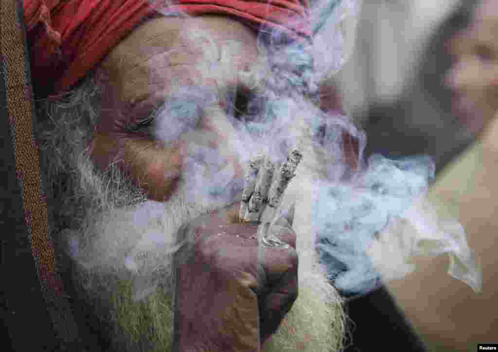 A devotee smokes hashish outside the shrine of Muslim Sufi Saint Data Ganj Bakhsh on his death anniversary in Lahore on January 2. Devotees started a three-day celebration of the 969th festival of Hazrat Ali Bin Usman, popularly known as Data Gunj Bakhsh. (Reuters/Mohsin Raza)