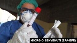Коронавирусты анықтайтын тест ұстап тұрған дәрігер. Италия, 18 наурыз 2020 жыл. Көрнекі сурет.