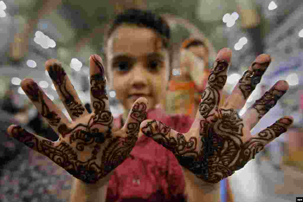 A young girl in Peshawar, Pakistan, applies a henna design on her hands ahead of the Eid al-Fitr festival marking the end of Ramadan. (epa/Bilawal Arbab)