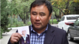 """Қытайдан көшіп келген Болатбек Рақымбайұлы """"Қытайда қамалған"""" 78 жастағы шешесінің суретін ұстап тұр. Алматы, 11 қазан 2018 жыл."""