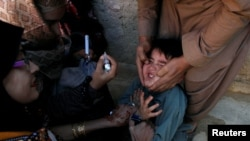FILE: A boy reacts as he is being administered polio vaccine drops by anti-polio vaccination workers in Quetta, the capital of southwestern Balochistan province.