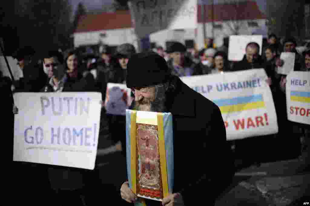 "A monk carries an icon and demonstrators hold placards reading, ""Putin go home!"" and ""Help Ukraine! Stop war!"" during an antiwar rally in front of the Russian Embassy in Kyiv on March 7. (AFP/Dimitar Dilkoff)"